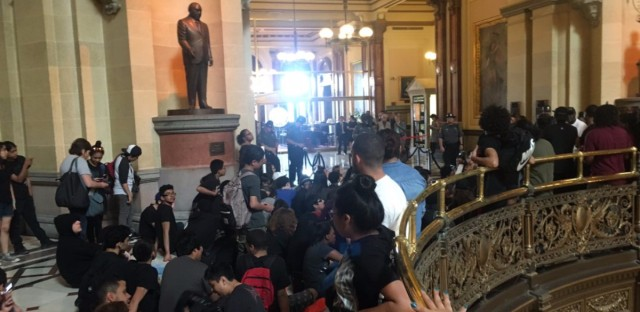Chicago Public Schools students sitting outside of the Governor's office while he was meeting with House Speaker Michael Madigan and other leaders.