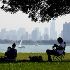 People rest under a tree during some hot weather at Montrose beach in Chicago on Wednesday, Aug. 31, 2011.
