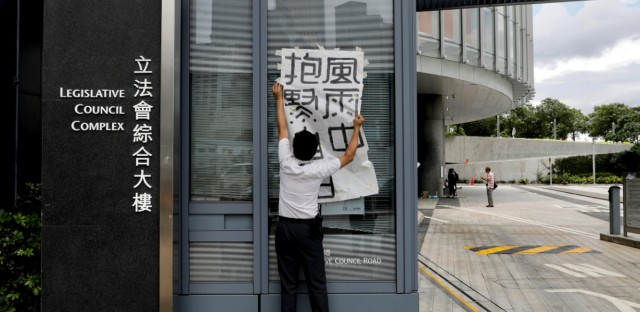 A security guard removes a poster which left by protesters outside the Legislative Council in Hong Kong, Tuesday, June 18, 2019. Hong Kong's government headquarters reopened Tuesday as the number of protesters outside dwindled to a few dozen and life returned to normal in the former British colony.