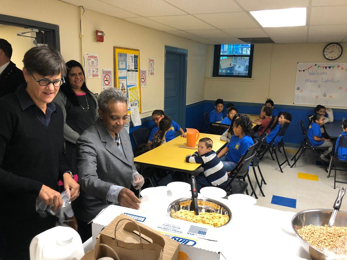 Mayor Lor Lightfoot serves breakfast in the foreground. Students sit at tables in the background.