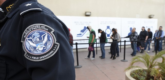 In this Dec. 10, 2015, file photo, pedestrians crossing from Mexico into the United States at the Otay Mesa Port of Entry wait in line in San Diego.