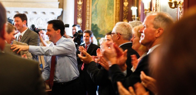 Wisconsin Gov. Scott Walker, center, is greeted by his cabinet and staff a day after he beat Milwaukee Mayor Tom Barrett in a recall election.