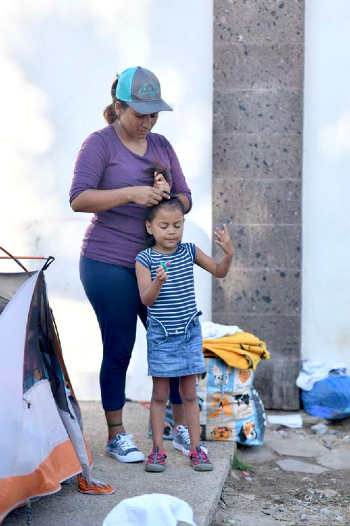 A woman fixes the hair of a child in Matamoros, Mexico