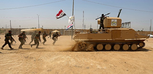hiite Volunteers fighters of the Imam Ali Brigade, an armed faction with the Iraqi Popular Mobilization Forces, train in their camp in Najaf, 100 miles (160 kilometers) south of Baghdad, Iraq.