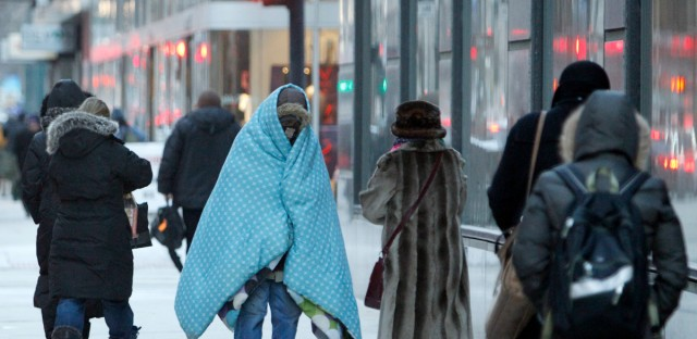 A homeless man who did not give his name bundles up in blankets Tuesday morning, Jan. 28, 2014, in downtown Chicago.
