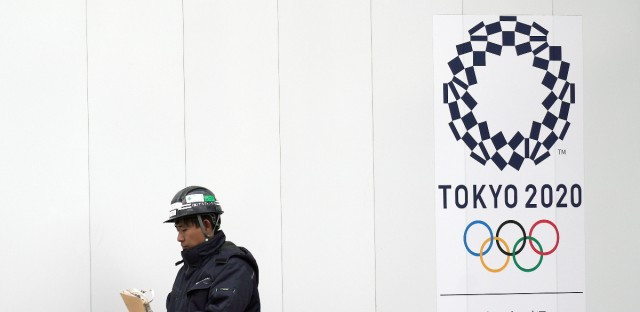In this Feb. 12, 2019, photo, a worker walks past one of construction sites for the Tokyo 2020 Olympics in Tokyo. The price of the opening and closing ceremony for the Tokyo Olympics has risen about 40 percent according to numbers released by the organizing committee.
