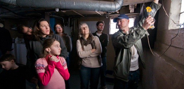 Huddled in their neighbors' basement, guests learned about energy efficiency from contractor Anthony Stonis.