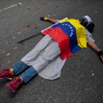 A protester covered by the Venezuelan flag lies on the ground during a protest against violence outside the Vatican's diplomatic mission in Caracas, Venezuela, Wednesday, Feb. 25, 2015. Protesters gathered here to ask Pope Francis to intervene after the death of a 14-year-old boy who was shot in the head Tuesday at an anti-government protest in the city of San Cristobal.