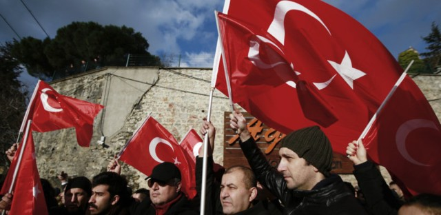 People wave Turkish flags as they march in Istanbul on Tuesday at a memorial for the victims of the nightclub attack on New Year's Day.