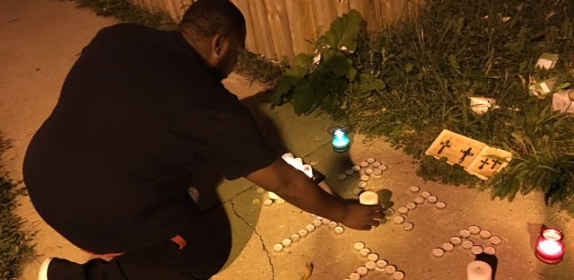 Jermaine Saffore lights candles for T.T. in front of a vacant lot where his family home used to sit on S. Kolin. T.T. was a transgender woman killed on Chicago's west side. Though she identified as female, the family still remembers T.T. as Tony.