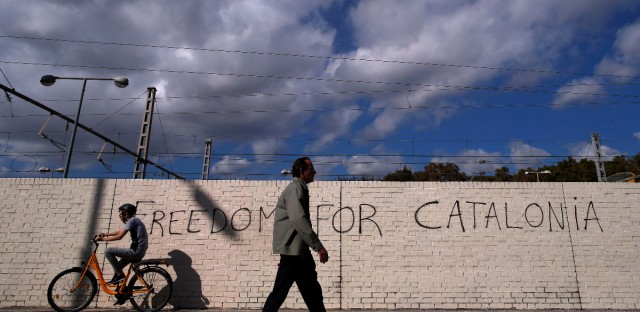 "People pass in front of graffiti reading ""Freedom for Catalonia"" in Barcelona, Spain, Monday, Oct. 23, 2017. Catalonia's regional parliament will hold a debate this week on Spain's plan to take direct control of the northeastern region — a session many fear could become a cover for a vote on declaring independence. (AP Photo/Manu Fernandez)"