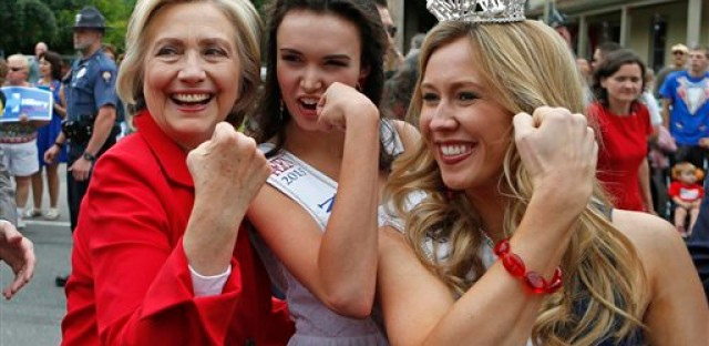 Democratic presidential candidate Hillary Rodham Clinton flexes her muscles with Miss Teen New Hampshire Allie Knault, center, and Miss New Hampshire Holly Blanchard, during a Fourth of July parade, Saturday, July 4, 2015, in Gorham, N.H.