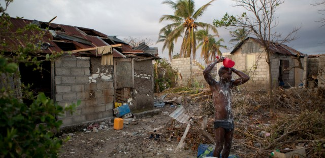 Yvald Saint Joy bathes in his backyard littered with debris caused by Hurricane Matthew, in Sous-Roche, Haiti
