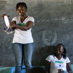 Faith Wanjoki of ZanaAfrica gives a lesson on how to use a sanitary pad in a classroom in Kisumu, Kenya. Her colleague, Catherine Onyango, sits by her side.