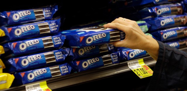 In this Feb. 9, 2011, file photo, a shopper selects Oreo cookies by Nabisco, which is part of the Kraft Foods Inc. family of brands and products, at a supermarket in Los Angeles. U.S. Republican presidential candidate Donald Trump is railing about what's wrong in corporate America as he woos voters fed up with the status quo. He is blasting drugmaker Pfizer's tax-saving plan to move its headquarters overseas, refusing to eat Oreo cookies made in Mexico and vowing to get Apple to make iPhones in the U.S. His tirades about unfair competition, tax evasion and lost jobs trumpet a familiar tune, but going further than many others running for president have dared. (AP Photo/File)