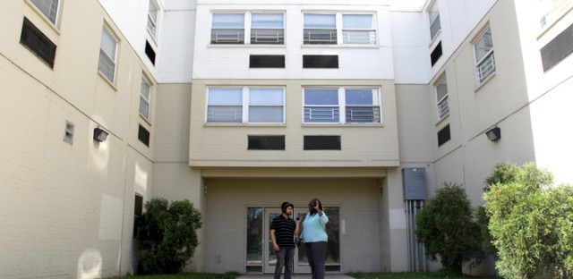 Tanveer Ali, left, and Crystal Palmer stand in her complex's courtyard. She says she could never live in the taller building, as she prefers her courtyard apartment.