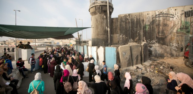 Palestinian women wait to cross the Qalandia checkpoint between the West Bank city of Ramallah and Jerusalem to attend the third Friday prayers in Jerusalem's al-Aqsa mosque, during the Muslim holy month of Ramadan, Friday, June 1, 2018.