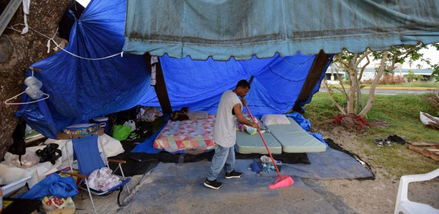 A resident sweeps at a camp set up on the shore of Laguna de Condado in San Juan, Puerto Rico, on Oct. 23, 2017.