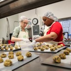 Elizabeth Bennett, director of partnerships for Together We Bake, and Nikki Yates, program participant, place cookie dough they've just made onto baking sheets.