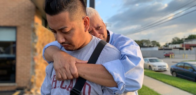 Edgardo Bartolome hugs his son, Aaron, as they wait outside the U.S. Immigration and Customs Enforcement facility.