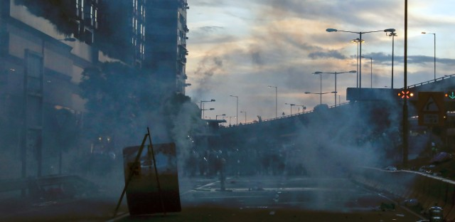 Smoke from tear gas is seen as riot policemen clear the protesters on a streets in Hong Kong, Sunday, July 28, 2019. Police launched tear gas at protesters in Hong Kong on Sunday for the second night in a row in another escalation of weeks-long anti-government and pro-democracy protests in the semi-autonomous Chinese territory.