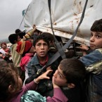 In this Monday, Dec. 10, 2012 photo, Syrian children who fled their homes gather around a vehicle to get pillows and blankets distributed at a camp for displaced Syrians, in the village of Atmeh, Syria.