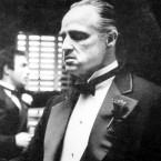 Amerigo Bonasera (Salvatore Corsitto) kisses the hand of Don Vito Corleone (Marlon Brando) in a scene from Francis Ford Coppola's The Godfather.