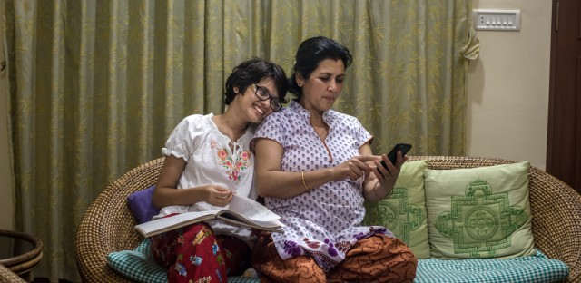 Prakriti Kandel and her mother look at pictures in their family album.