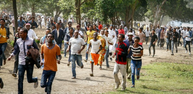 In this photo taken on Sunday, Oct. 2, 2016, people run during a stampede in Bishoftu, Ethiopia. Violence flared again Monday in Ethiopia's restive Oromia region, where dozens of people were killed a day earlier in a stampede when police tried to disrupt an anti-government protest amid a massive religious festival. Clashes between security forces and protesters erupted Sunday evening and continued Monday morning in the towns of Bishoftu and Ambo, an Ethiopian government official and witnesses told The Associated Press.
