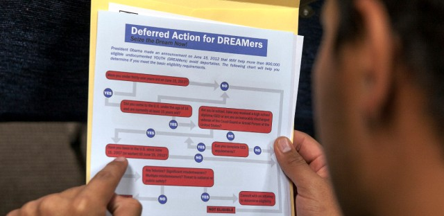 An immigrant reads the conditions needed to apply for the Deferred Action for Childhood Arrivals (DACA) program at the Coalition for Humane Immigrant Rights offices in Los Angeles on Wednesday, Aug. 15, 2012.