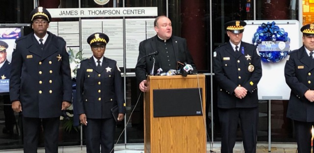 "Chicago police chaplain Father Dan Brandt stands alongside the other Chicago Police Department chaplains at a memorial for slain Cmdr. Paul Bauer. ""We come together today both to mourn, to remember, but also to give thanks, thanks to God for Paul,"" Brandt said on the one-year anniversary of Bauer's death."