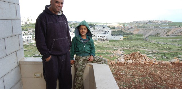 Nabil Bisharat (with his 8-year-old son) worked his way up over six years from the assembly line to management at SodaStream but recently lost his permit to work at the company's new facilities in Israel. He bought the empty land seen here behind his home with his high earnings at the Israeli company. Israel's government says its policy is to encourage jobs for Israeli citizens.