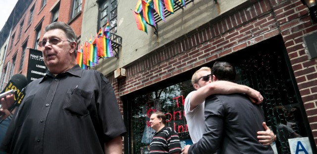 "Stonewall Inn's bartender who goes by the single name of Tree, far left, is interviewed while a couple, right, requesting anonymity, kiss outside the iconic Greenwich Village bar, Friday, June 26, 2015, in New York. ""I was here dancing with my friends the day of the rebellion when the cops raided the place,"" said Tree about 1969 event credited for igniting the gay rights movement. The Supreme Court declared Friday that same-sex couples have a right to marry anywhere in the U.S."