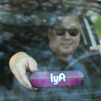 A Lyft driver places a company emblem on his dashboard Jan. 31, in San Francisco. Lyft announced it's offering education benefits, a move aimed at recruiting and retaining drivers in its competition with Uber. Kelly Sullivan/Getty Images for Lyft