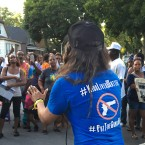 """Community activist Aleta Clark speaks to residents and police gathered for an """"Operation Wake Up"""" rally in Chicago. At least 15 children age 12 years old and younger have been injured by gunfire since the beginning of the year."""