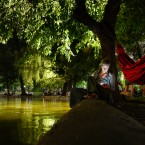 In this Tuesday, Aug. 13, 2019 photograph, a woman looks at a mobile phone while sitting by the Cismigiu lake on a hot evening in Bucharest, Romania. People gathered for a night picnic in the Cismigiu Gardens to take advantage of the slightly cooler air, as the Romanian capital and most of the country are still affected by a heat wave with day-time temperatures in the shade reaching 38 degrees Centigrade (100.4 Fahrenheit).