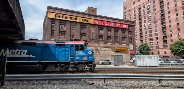 A Metra train passes behind the Cassidy Tire building. In the early 1900s, this building was moved to make way for train tracks.