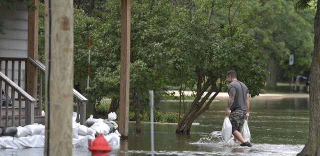 A man carries sandbags to reinforce the barrier he build to keep the floodwater from reaching his house in Gurnee, Ill., Friday. Illinois officials say flood damage north of Chicago is expected to worsen this weekend as water flows down rivers.