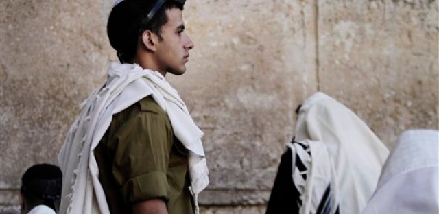 An Israeli soldier prays next to the Western Wall, the holiest site where Jews can pray, in Jerusalem's Old City on July 2, 2012. Israel's prime minister on Monday dissolved a high-profile committee assigned to reform the country's military draft law to spread the burden among more sectors of society, conscripting ultra-Orthodox Jews and requiring Israeli Arabs to do civilian service.