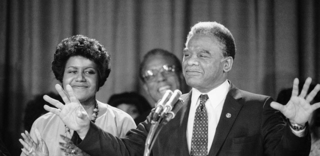 Chicago mayor-elect Harold Washington appears before a crowd of supporters after being elected mayor of Chicago on Wednesday, April 13, 1983 in Chicago. Washington's fiancé, Mary Smith is at left.