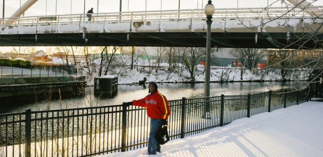 """J.L. Gross walks along a river pathway near the Lathrop Homes. He has lived in the development for 27 years and cherishes Lathrop because """"it gives us a sense of community to live here — in a project setting you generally don't have that."""""""