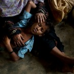 A Rohingya woman comforts her exhausted son as they take shelter inside a school after having just arrived from the Myanmar side of the border at Kutupalong refugee camp, Bangladesh, Thursday, Sept. 7, 2017.