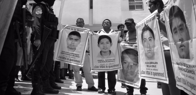 Parents of the 43 missing students of Ayotzinapa Rural Teachers' College confront state anti-riot police. After government corruption surfaced following the students' disappearance, demonstrators hoped to invalidate midterm elections in the state of Guerrero by boycotting the vote and preventing the installation of polling stations.