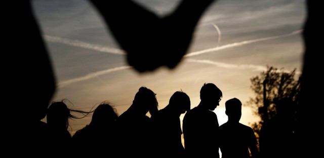 "Youths hold hands for a prayer during a gathering at sunset outside the Christian Fellowship Church in Benton, Ky in April 2016. Americans who say they have no ties to organized religion, dubbed ""nones,"" now make up about 23 percent of the population, just behind evangelicals, who comprise about 25 percent, according to the Pew Research Center. (AP Photo/David Goldman)"
