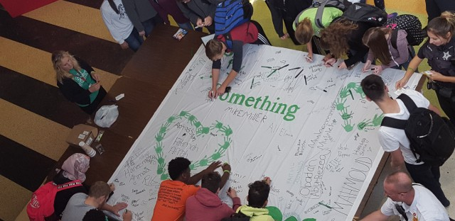 "Stagg High School students sign a banner pledging to speak up and ""say something"" to an adult if they notice warning signs."