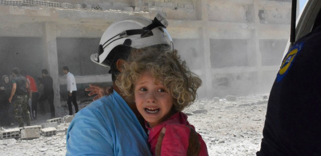 A civil defense worker carrying a child after airstrikes hit a school housing a number of displaced people, in the western part of the southern Daraa province of Syria, Wednesday, June 14, 2017.