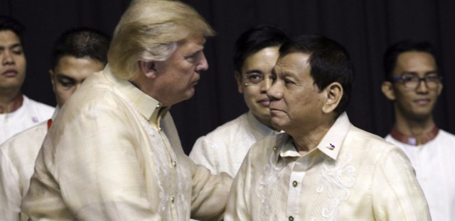 President Trump shakes hand with Philippines President Rodrigo Duterte during the gala dinner marking ASEAN's 50th anniversary in Manila, Philippines, on Sunday. Athit Perawongmetha/AP