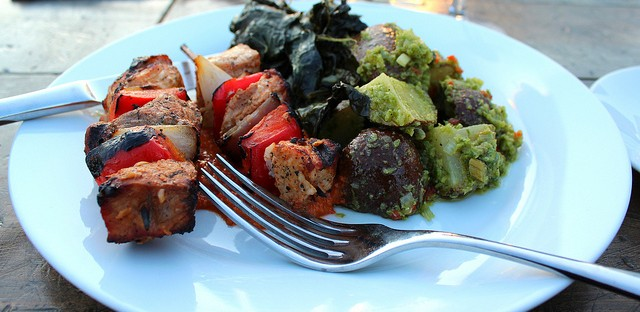 Grilled pork pinchos with romesco, City Farm garlic scape potato salad, wilted chard, and lacinto kale by FIG Catering in Chicago