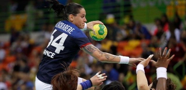 France's Alexandra Lacrabere, top, jumps over teammate Laurisa Landre and South Korea's Yoo Hyun-ji, left, during the women's preliminary handball match between South Korea and France at the 2016 Summer Olympics in Rio de Janeiro, Brazil on August 12, 2016.