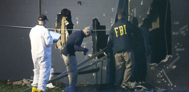 FBI agents inspect the rear wall of the Pulse Orlando nightclub in Orlando, Fla., where authorities say 49 victims died Sunday. The gunman, identified as Omar Mateen, was killed by police.